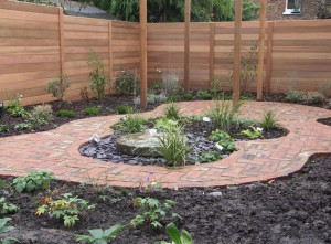 Brick paver path around millstone water feature with cedar fencing