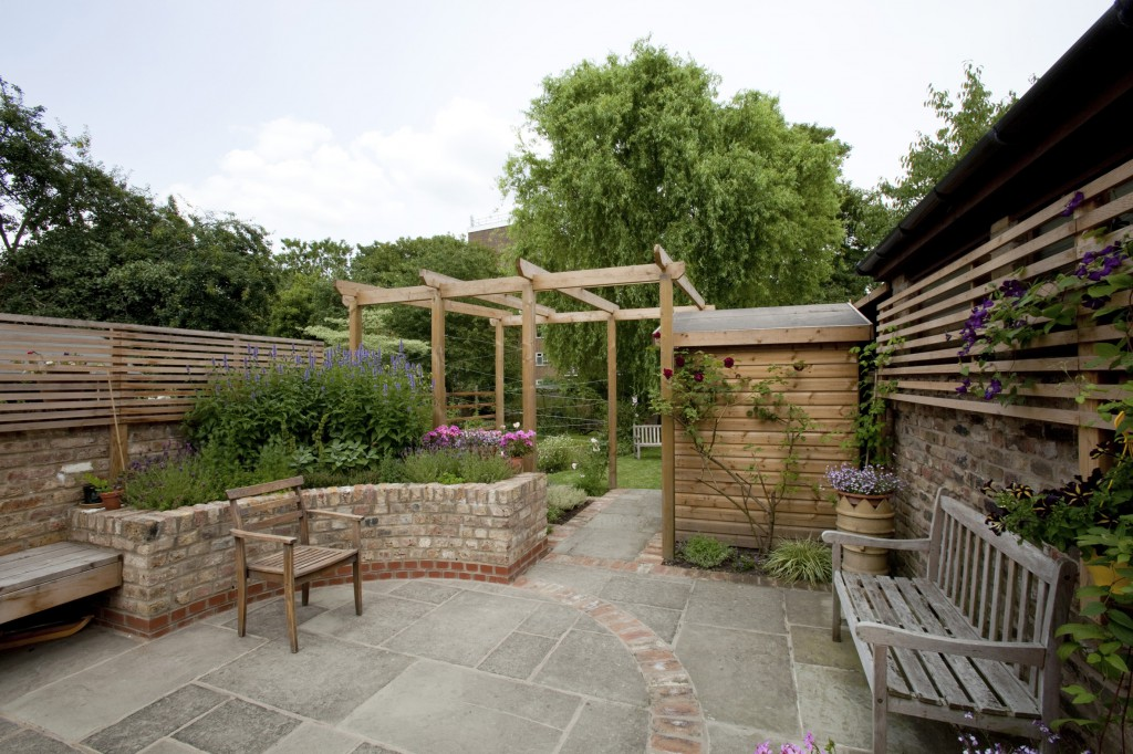 this long narrow garden in stoke newington feels spacious with its open boundaries and curving path of clay pavers from the patio and pergola - Garden Design Long Narrow