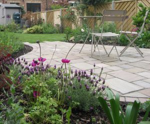 Tumbled sandstone setts in different shades complement the colourful planting